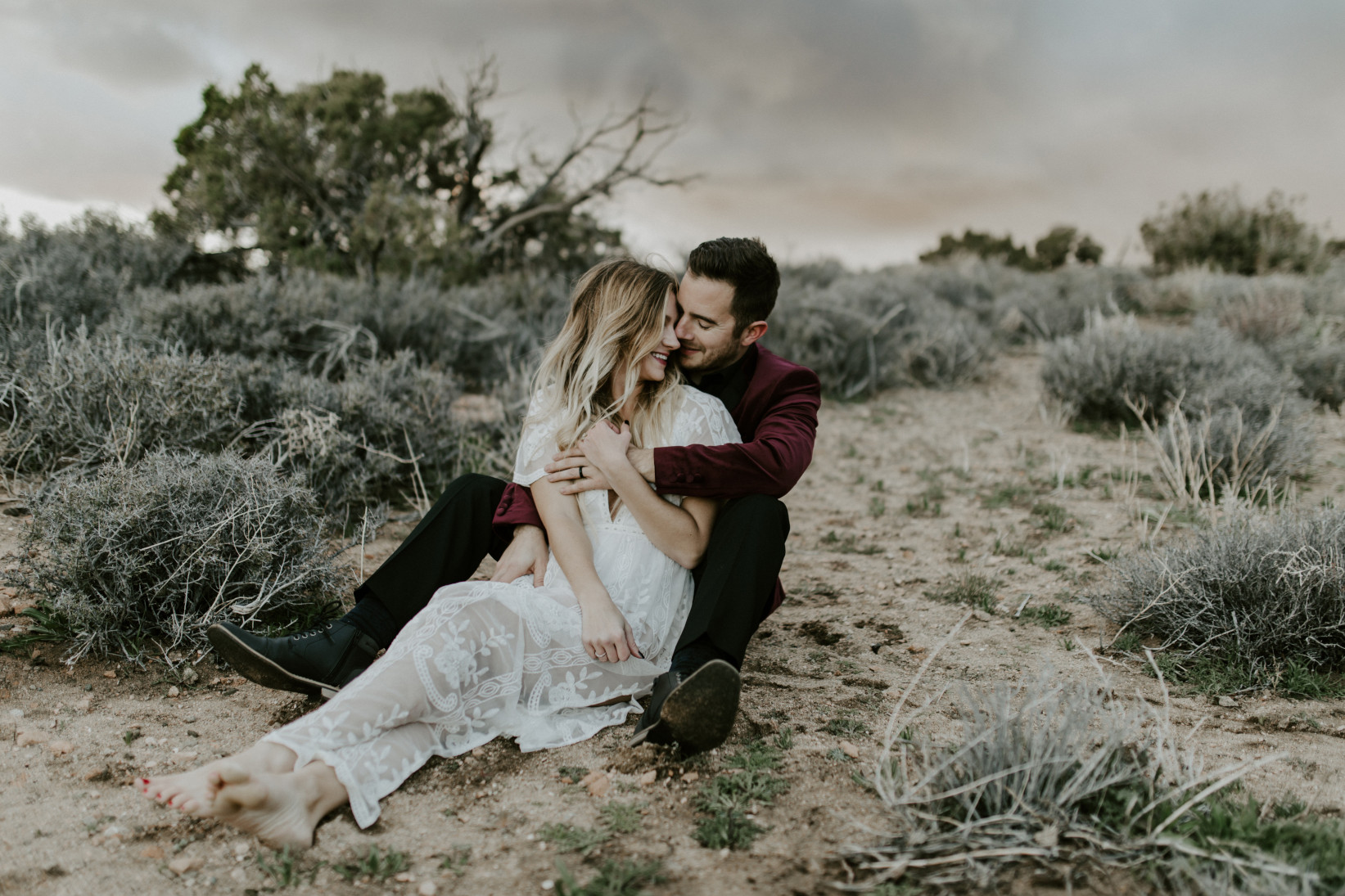 Jeremy and Alyssa sit on the sand at Joshua Tree National Park, CA Elopement wedding photography at Joshua Tree National Park by Sienna Plus Josh.
