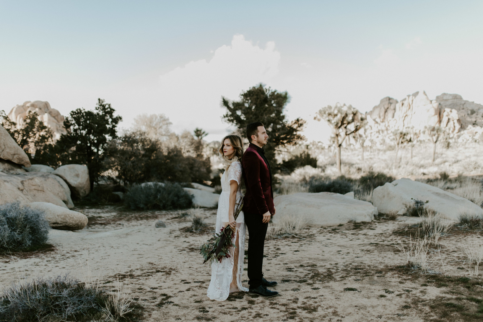 Alyssa and Jeremy stand back to back at Joshua Tree National Park. Elopement wedding photography at Joshua Tree National Park by Sienna Plus Josh.