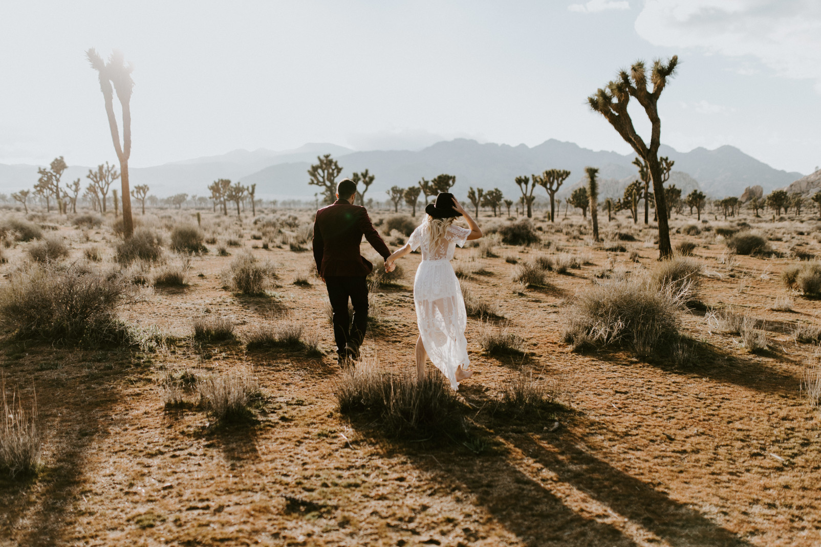 Alyssa and Jeremy walk through Joshua Tree National Park, CA Elopement wedding photography at Joshua Tree National Park by Sienna Plus Josh.