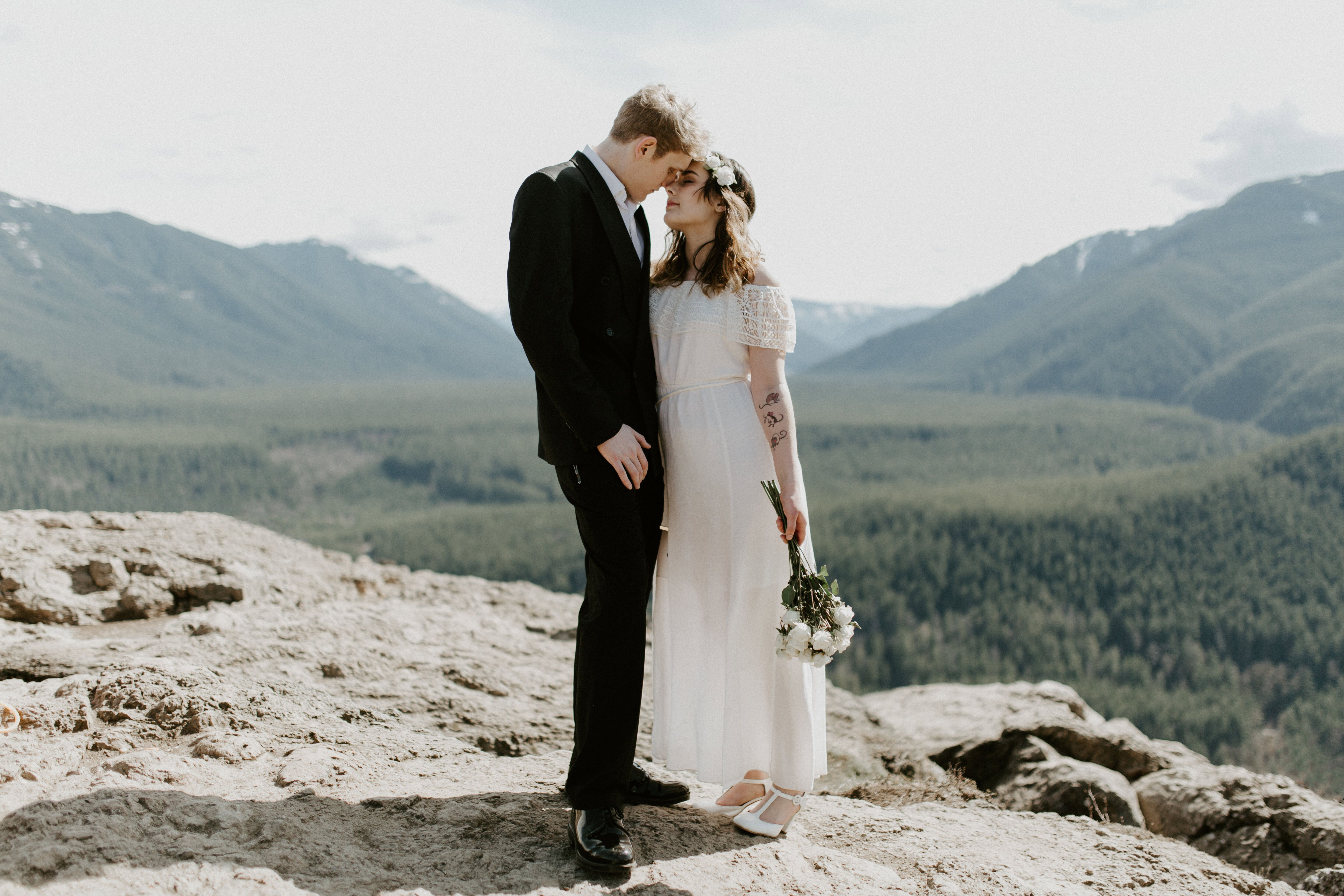 Michael and Winnifred kiss while standing near the cliff of Rattlesnake Ledge. Elopement adventure shoot at Rattlesnake Ledge, Washington.