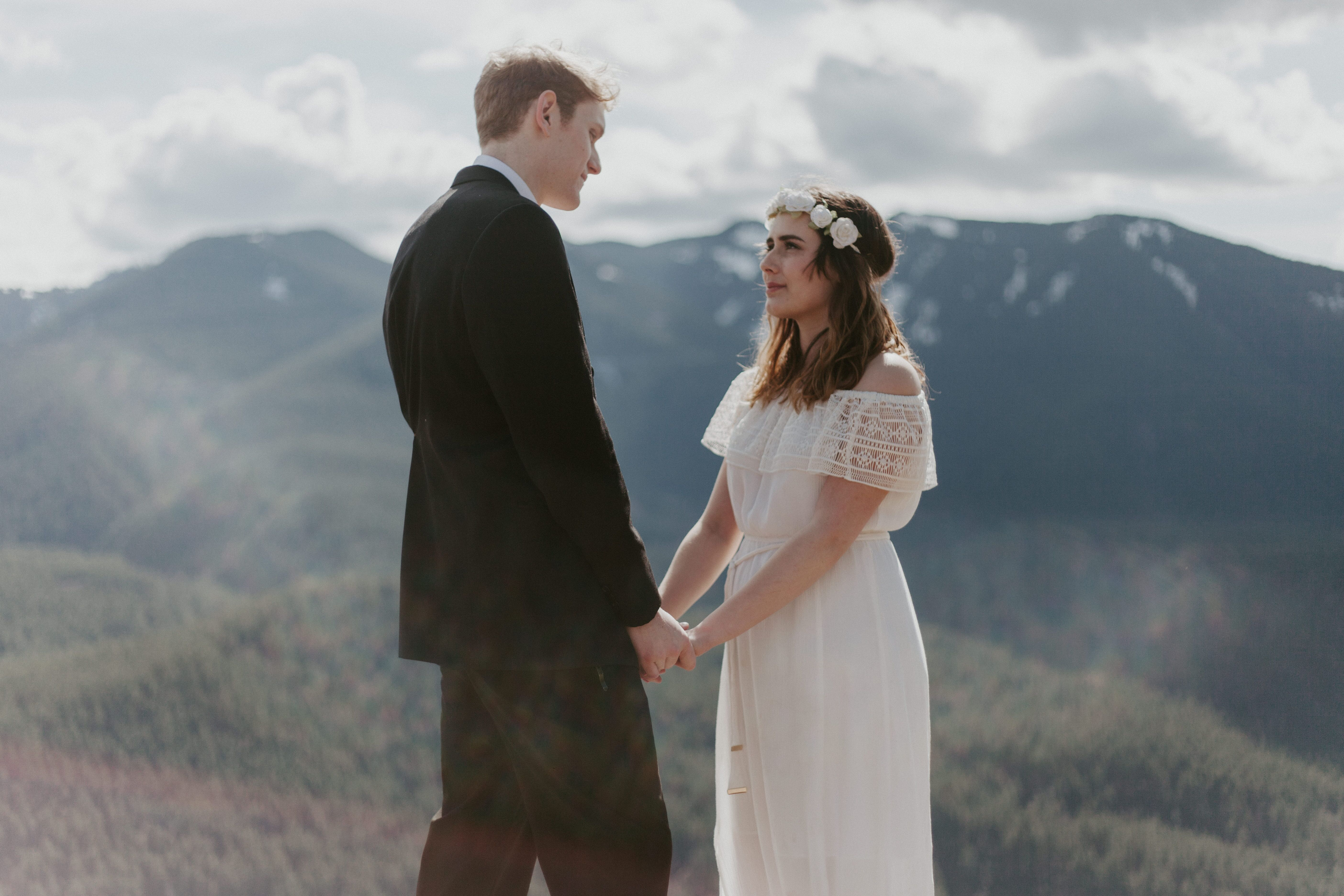 Michael and Winnifred hold hands with a view of Washington state in the background. Elopement adventure shoot at Rattlesnake Ledge, Washington.
