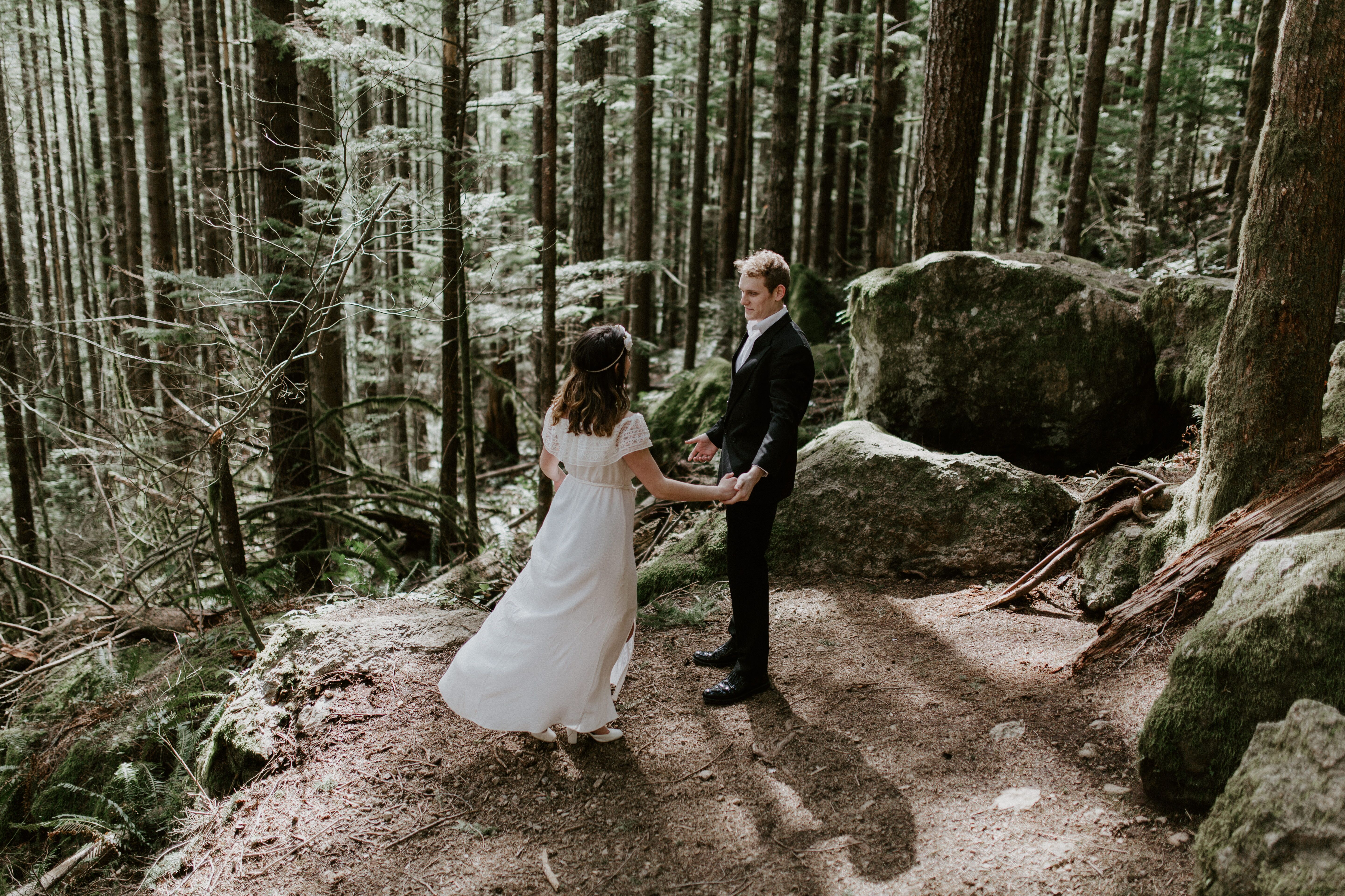 Michael and Winnifred dance near the trees on the trail to Rattlesnake Ledge. Elopement adventure shoot at Rattlesnake Lake, Washington.