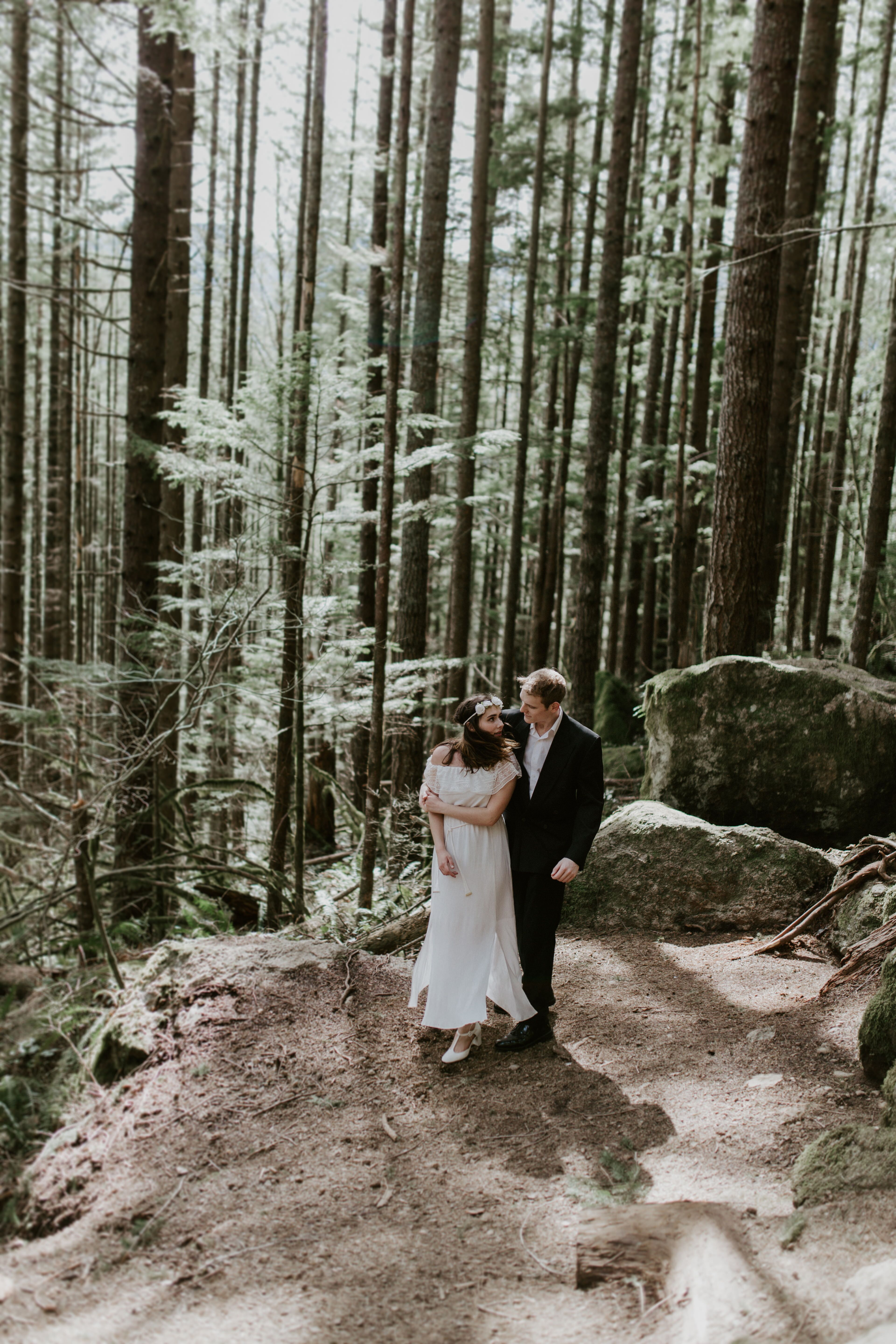 Michale and Winnifred dance near the tress on the trail to Rattlesnake Ledge. Elopement adventure shoot at Rattlesnake Lake, Washington.